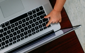 Laptop with toddler's finger pressing a key
